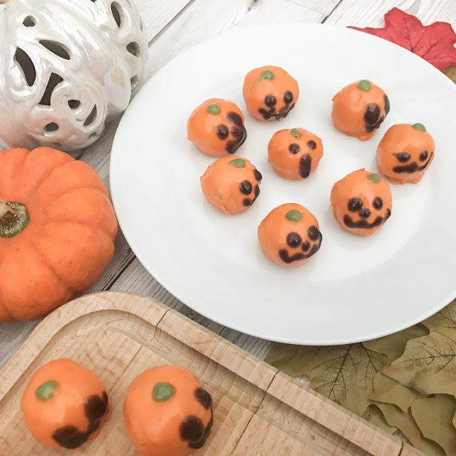 Marzipan Pumpkin Bites on a plate and chopping board, surrounded by pumpkins