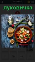 на столе стоит миска с салатом и рядом положена луковичка