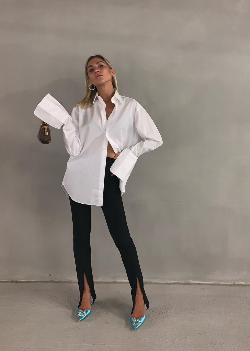 Fashion-forward summer wedding guest outfit idea from Natalia Georgala in a white button down shirt with statement cuffs, mini bag, black pants with ankle slits, and green embellished heels