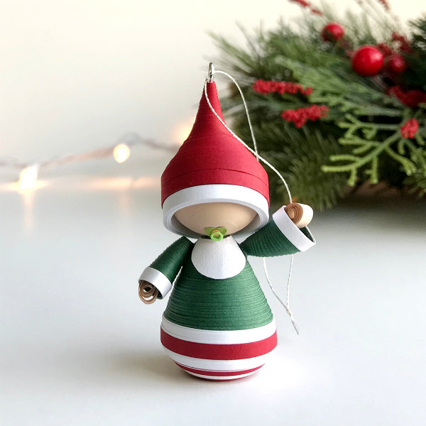 tiny quilled baby Christmas tree ornament dressed in red, green, and white with green pacifier