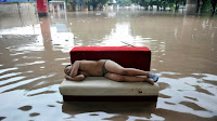 A child sleeps on a couch in a flooded street in Chongqing, China, on July 20, 2010 (Credit: Reuters) Click to Enlarge.