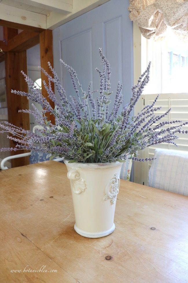 Faux lavender stems in a French style ceramic pot look realistic