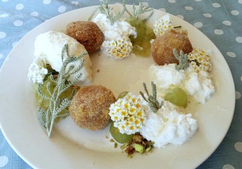 Un plato adornado con flores, croqueta, nata y helado