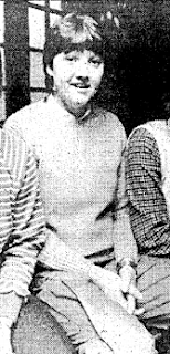 A black and white image of a smiling woman with short dark hair