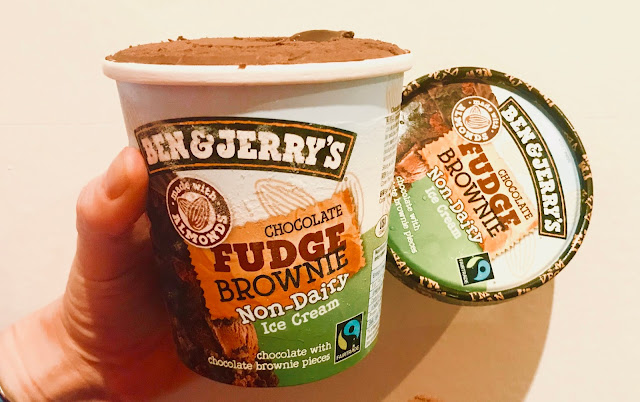 A hand holding an opened tub of vegan dairy free Ben & Jerry's ice cream