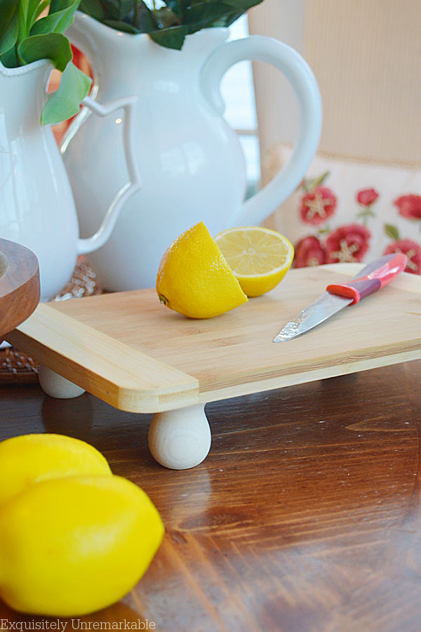 Raised Cutting Board on table with cut lemons on top