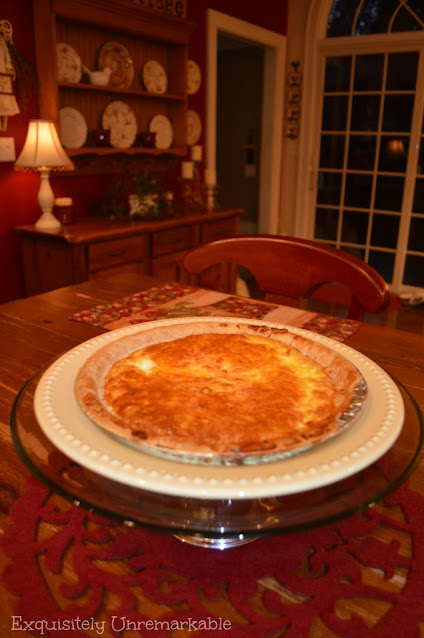 Quiche on a glass plate rack in a red kitchen