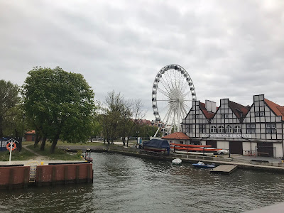 big wheel of gdansk in the background of the water way with trees and buildings alongside