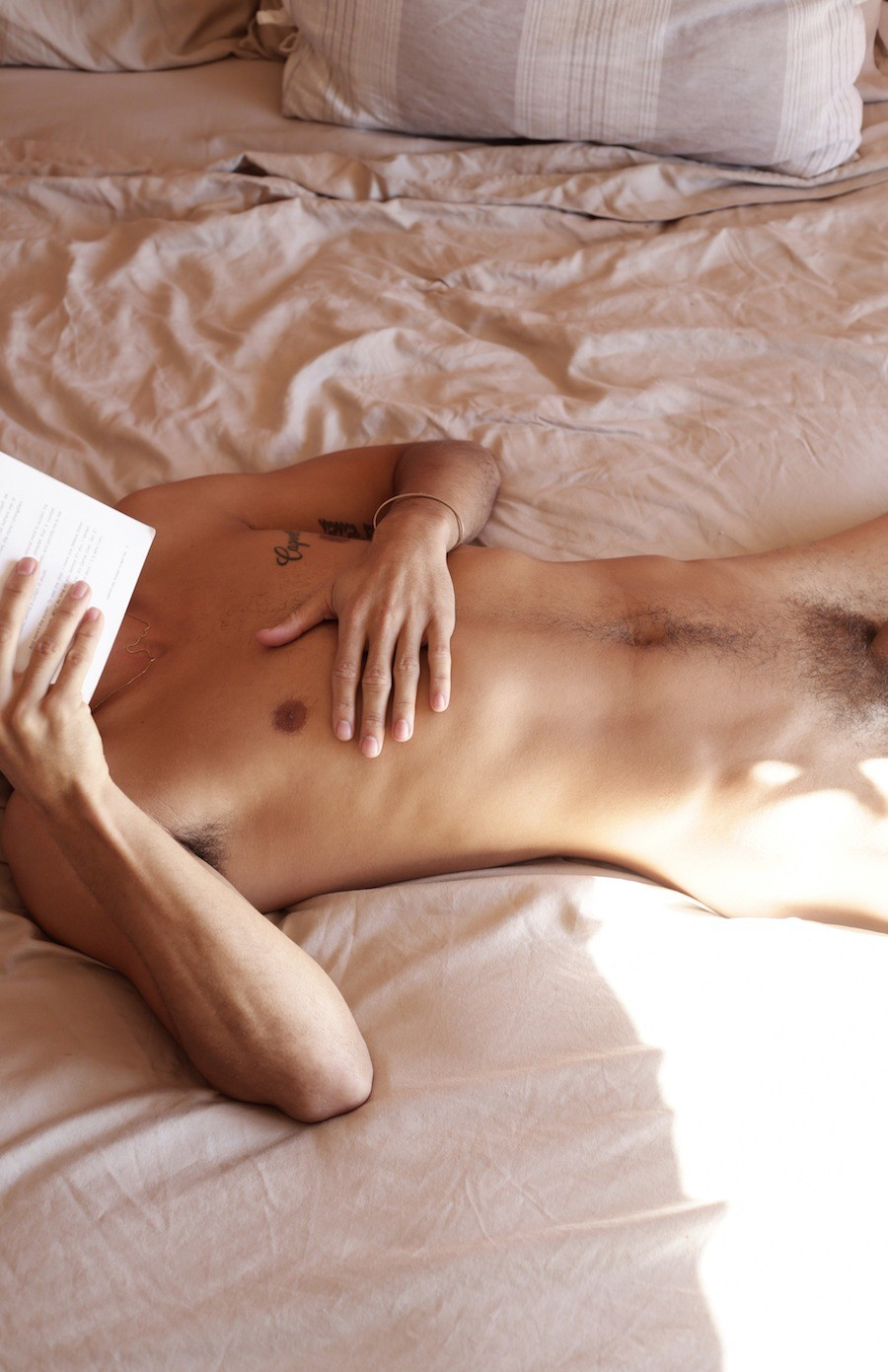 Nude hairy man laying on a bed