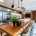 Espaço gourmet com frontão nicho, painel de madeira ferro e ilha com mesa tora - lindo!