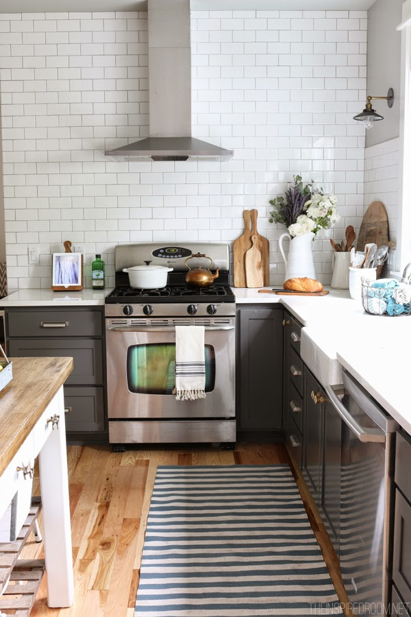 Gorgeous cabinets painted in Benjamin Moore Kendall Charcoal with white subway tile. Swooning! From The Inspired Room.