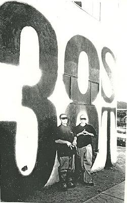 Dos miembros de la pandilla Calle 38 junto a un graffiti de la banda