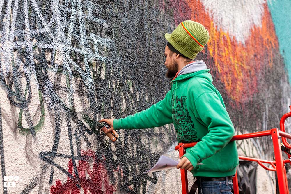 Street Artist Lousi Masai at work on a mural in Walthamstow, London