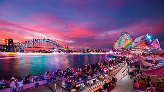 """Vivid Festival là một lễ hội trình diễn ánh sáng kéo dài 23 ngày trong tháng 5 và tháng 6 tại Sydney. Phần tuyệt nhất của lễ hội đó chính là """"sự tương tác"""". Năm ngoái, người xem đã trầm trồ bởi sự thay đổi màu sắc của cầu Cảng Sydney và sự sáng tạo với chiếc ghế sáng lên theo nhịp đập của trái tim bạn."""