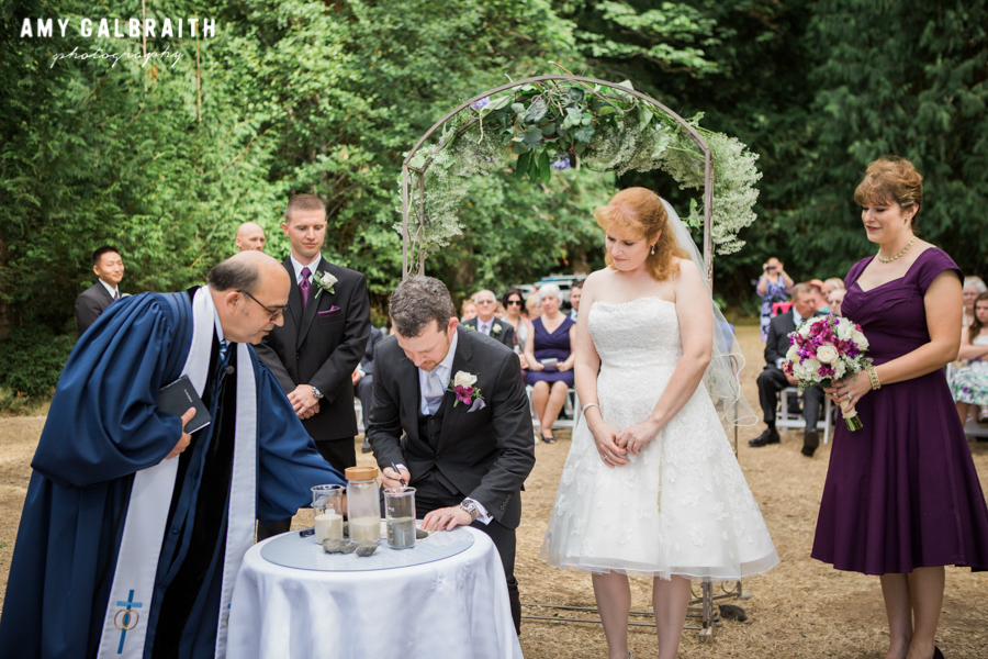 groom signing marriage certificate at outdoor wedding ceremony