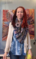 image of youth librarian, Ms. Nicole with a colorful scarf on and colorful painting in the background