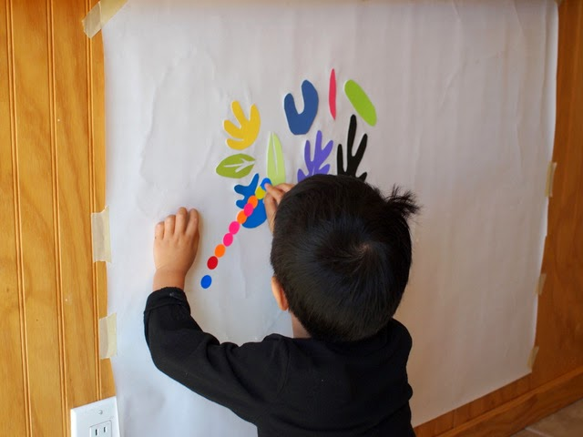 child sticking on stickers onto matisse inspired murals