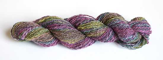A skein of hand spun mystery wool yarn dyed in a rainbow of colors on a white background.