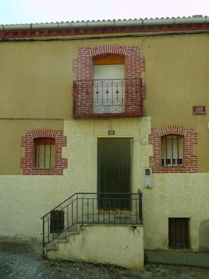 casa de dos pisos que parece habitada. Fachada enfoscada en tono ocre, cercos de las ventanas y balcón en ladrillo visto