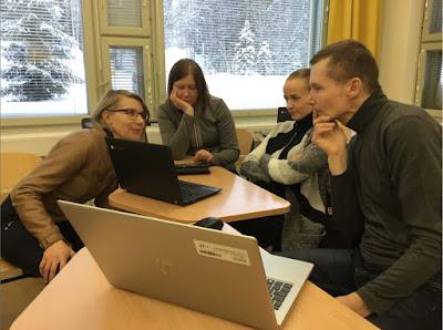 Neljä opettajaa tutkii läppäreiltä Quizlet-peliä luokkahuoneessa. Ikkunoista näkyy luminen maisema.