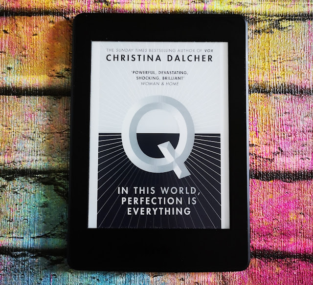 image of the front cover of the book Q by Christina Dalcher displayed on a Kindle Paperwhite and laid on a faux bright background that has been brightly painted. The cover features a simple half black, half white design with a large letter Q in the centre. The authors name Christina Dalcher is displayed as well as an emblem indicating the author also wrote 'Vox'.