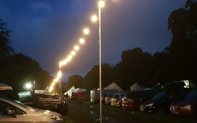 Just So Festival Friday night scene showing parked cars, tents and rain puddles