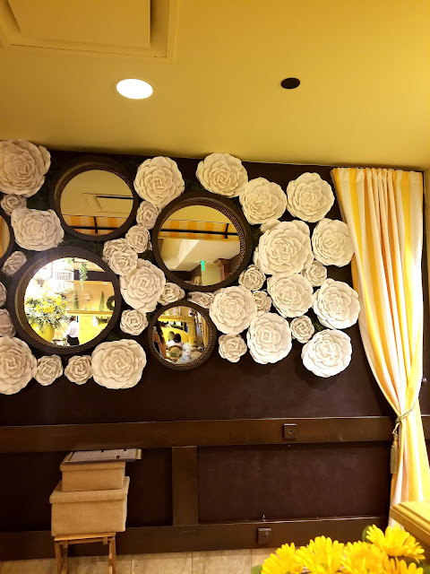circle mirrors wallflowers Yellow Vase Cafe South Coast Plaza Orange County California flowers sunflowers French restaurant striped curtain