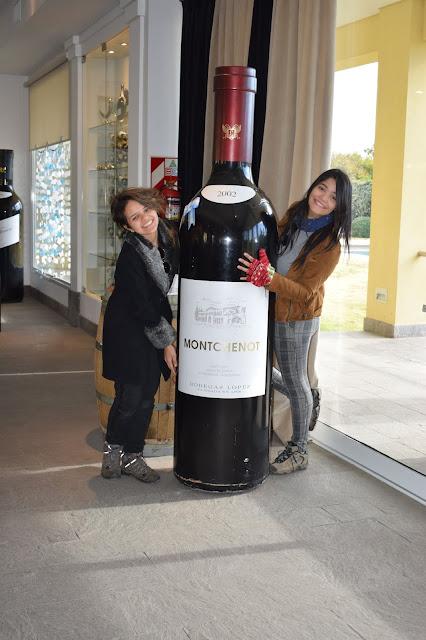 duas meninas abraçando uma garrafa grande de vinho