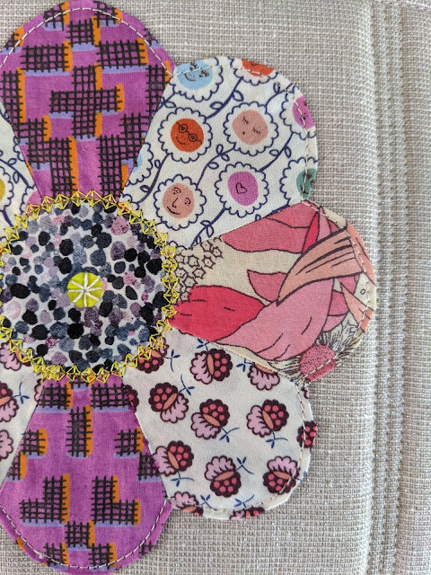 close up of applique dresden plate flower on quilted background
