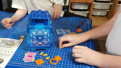 2 children playing Bank Attack! family electronic safe cracking game