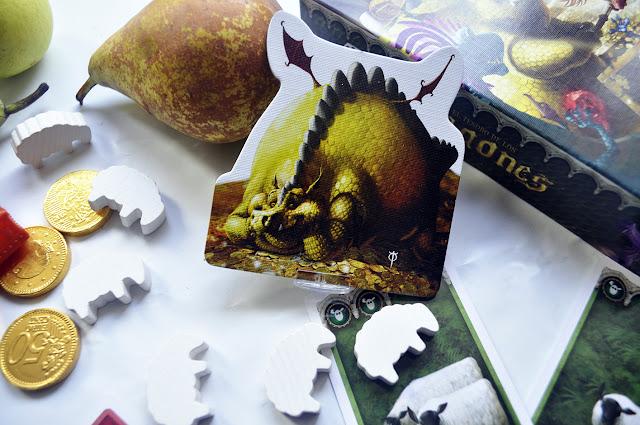 Primer plano de una ficha de un dragón muy gordo tumbado sobre un tesoro