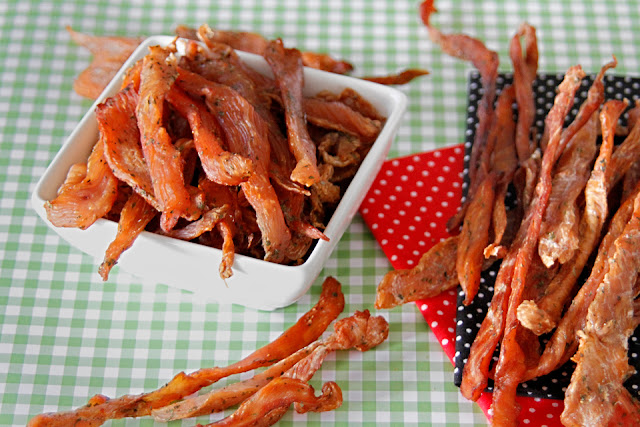 Chicken jerky dog treats in a bowl on polka dot napkins