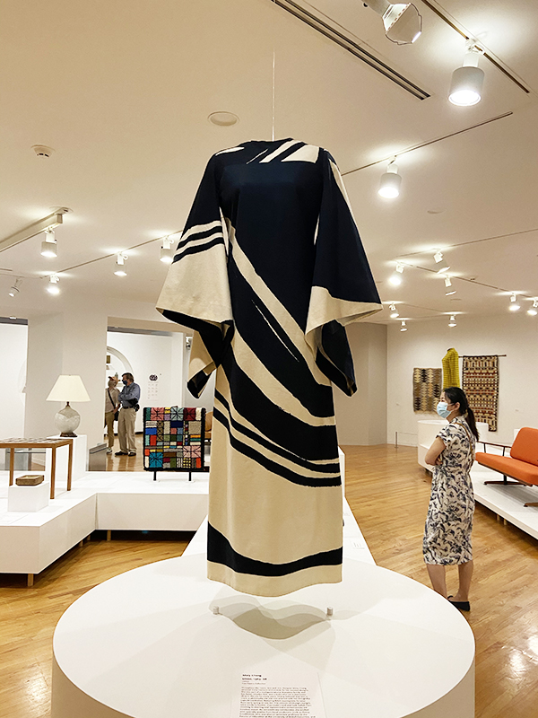 A black and white caftan-esque dress from the 1960s with flowing sleeves is on display in the foreground, while art gallery patrons admire other pieces on display in the background. Part of the 'Modern in the Making: Post-War Craft and Design in British Columbia' exhibit at the Vancouver Art Gallery.