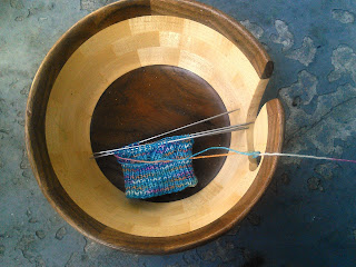 A pair of socks on double-pointed needles.  The yarn is blue flecked with yellow, white, and pink.