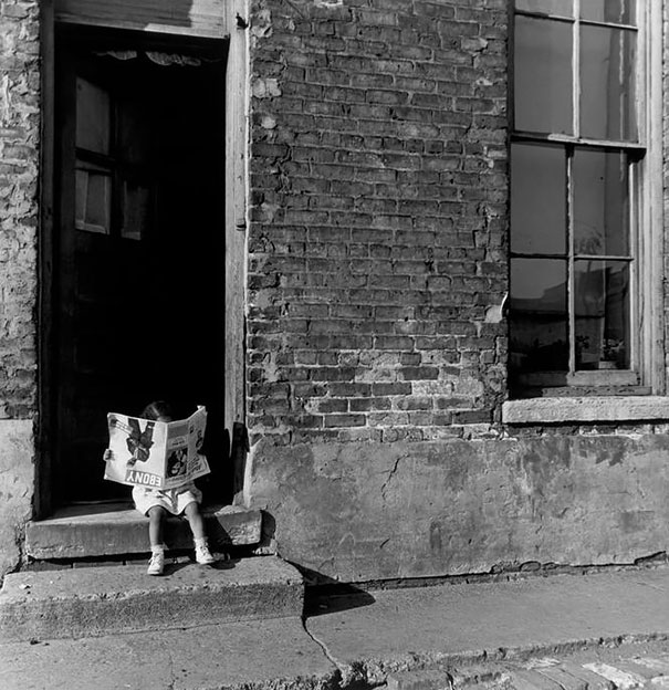 Vintage photo little girl reading Ebony Magazine upside down in the doorway. Chicago, 1947. Little Scraps of Wisdom. marchmatron.com