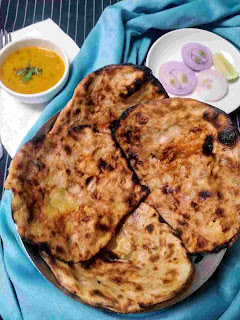 Serving amritsari kulcha in a bread basket dal and onion slices in background