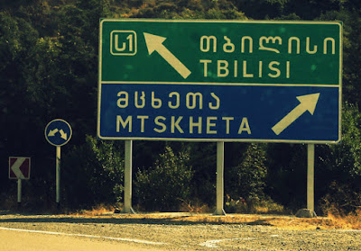This green and blue road sign gives directions to Tbilisi and Mtskheta in both Latin and Georgian script.