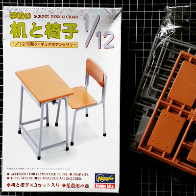 Pieces of a 1/12 scale kit for a school desk and chair next to the box they came in.
