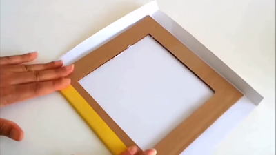 Setelah dilumuri lem, tempelkan satu sisi kardus yang dilumuri lem ke kertas kado