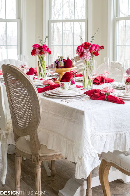 red velvet hearts and a bouquet of flowers create a dramatic splash of color on this Valentines table