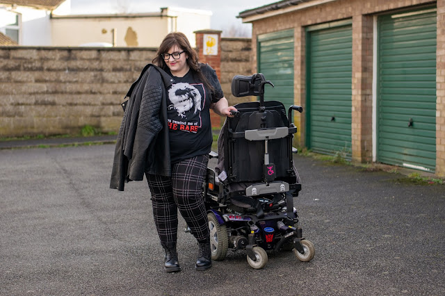 Woman stood next to wheelchair wearing Bowie from Labyrinth tshirt, red and black check trousers, black Dr Marten boots and holding a leather jacket over shoulder