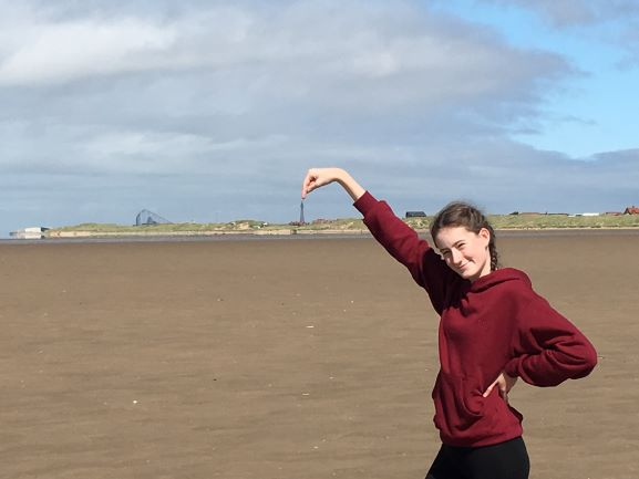 teen on beach, pointing to Blackpool Tower
