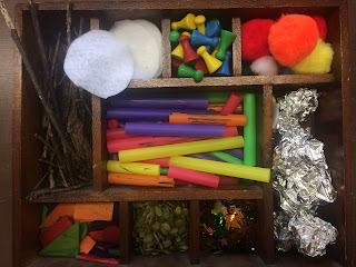 wooden box with several compartments filled with small items like beads, sticks, and plastic drinking straws