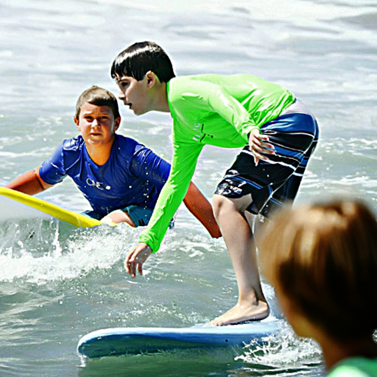 11 year old boy camper at Aloha Beach Camp Summer Camp surfs the waves on his blue surfboard while other campers watch.