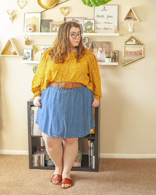 An outfit consisting of a microfloral mustard yellow long sleeve off the shoulder blouse half tucked unto a denim skater skirt and brown slide sandals.