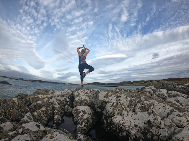 woman stretching on rock with beach and white clouds in background