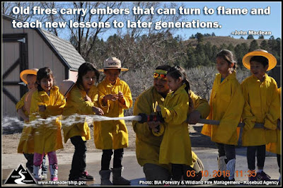 """Old fire carry embers that can turn to flame and teach new lessons to later generations."" John Maclean (Children dressed as wildland firefighters and spraying water)"