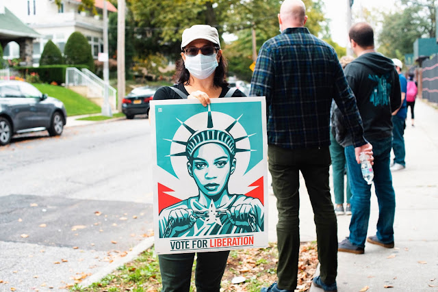žena stojící s plakátem sochy svobody u amerických prezidentských voleb