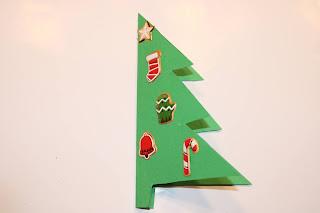 Postal em forma de Árvore de Natal, dobrado ao meio, decorado com autocolantes
