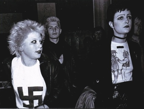 Siouxsie Sioux with a young Billy Idol in the background.  PunkMetalRap.com